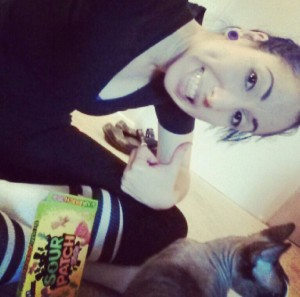 Me celebrating getting cleared for PFM with a box of Sour Patch kids and a cat.